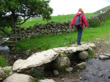 Walker crossing clapper bridge near Dufton Pike © NPAP/Elizabeth Pickett